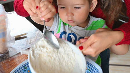 mother and child sift flour through a sieve. High quality photo