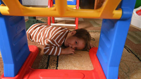 the child lies under the table. High quality photo