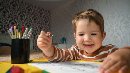 the child draws happily while sitting at the childrens table