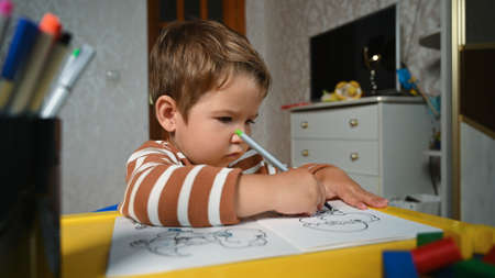 the child draws independently at the table Reklamní fotografie