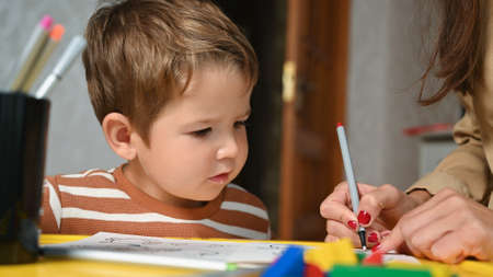 child paints coloring book with mother
