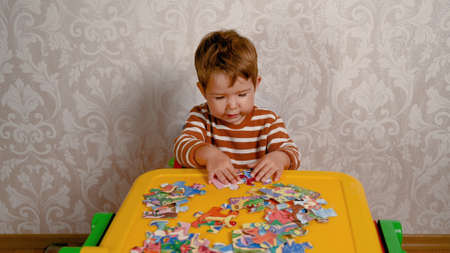 child collects puzzles at the table