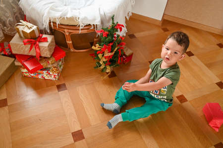 Child near a small Christmas tree, top view. High quality photo