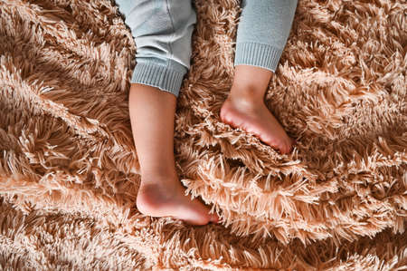 ? ute little baby feet on fluffy plaid background. Deep dream. Daily regime. Child development and health. High quality photo