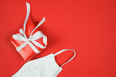 Christmas during the coronavirus epidemic. Gift box with ribbon and face mask on a red background. High quality photo