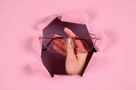 Hand holds glasses on a pink background. High quality photo Zdjęcie Seryjne