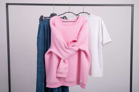 Women's minimal fashion pastel clothes. Stylish female t-shirts, hoodie, pants on hanger on white background. Fashionable, modern, youth clothes. Clothing made from natural materials, cotton. High quality photo Stock fotó