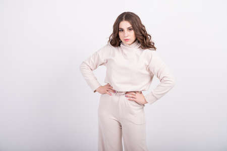 Young woman in beige jersey suit. The concept of casual comfortable women's clothing in pastel shades, basic wardrobe. Zero waste concept. High quality photo