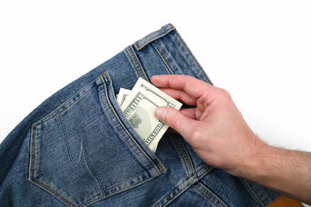 hand takes dollar bills in the back pocket of jeans. High quality photo
