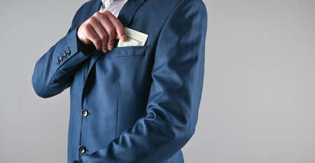 man in suit puts money in his pocket, corruption concept. High quality photo