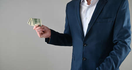 a man in a suit holds money in his hands. High quality photo