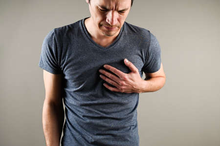 Young caucasian man grabs his hands for heart, heart attack. Heart problems concept. Medical and pharmaceutical concept. High quality photo
