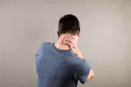 Man massaging his neck on gray background. Suffering from discomfort long hours of sedentary overworking concept. High quality photo
