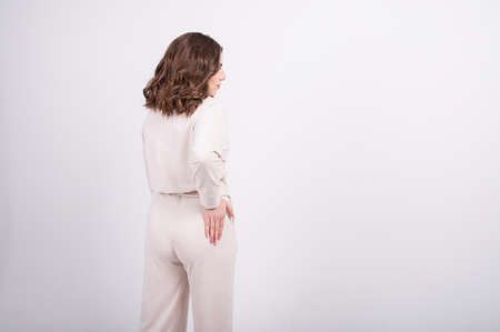 Back view of a woman in fashionable pastel suit made from natural fabrics. Capsule wardrobe concept. Zero waste shopping. High quality photo