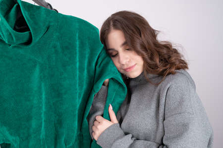 Young caucasian woman in the store examines and chooses clothes. Womens clothing made of natural eco-friendly soft materials 版權商用圖片