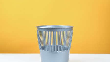 gray trash can on yellow background 版權商用圖片