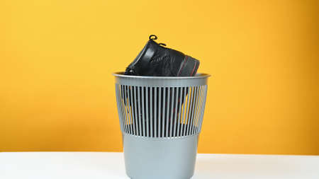 A man throws a pair of leather shoes into a plastic bucket on yellow background. Conscious consumption concept