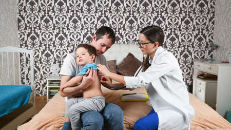 The doctor examines a sick child at home 版權商用圖片