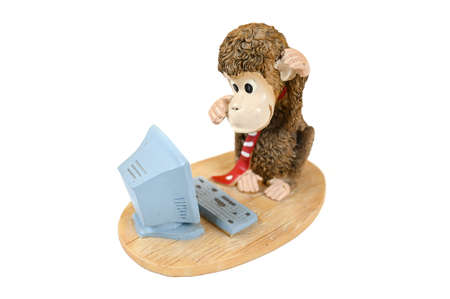 Monkey at the computer, statuette on an isolated background. High quality photo