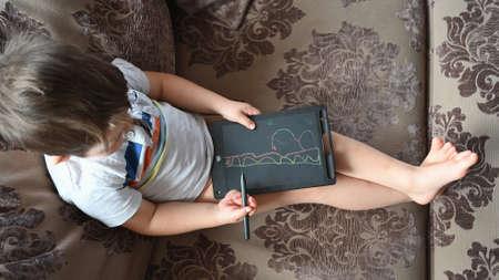 Cute Caucasian boy with draws on tablet, sitting on the sofa. High quality photo 版權商用圖片