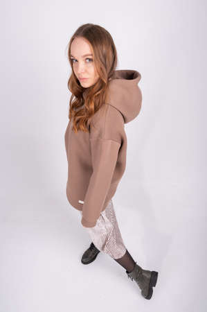 Portrait of young beautiful redhead woman in cozy clothes. Sexy female fashion model poses in taupe hoodie and skirt on white studio background. High quality photo