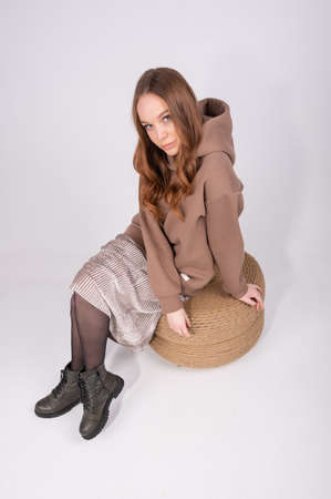 Fashionable redhair woman in hoodie, skirt and stylish rough shoes sitting on pouf in studio. High quality photo 版權商用圖片
