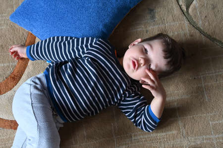 Sad little child lies on the floor, top view. High quality photo