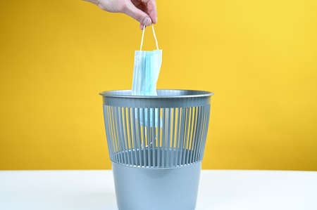 Hand throws the mask into the trash bin on a yellow background. High quality photo