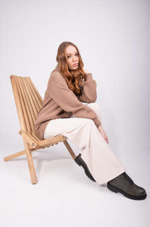 Beautiful woman with curly red hair in beige pants and a taupe hoodie sitting in wooden armchair on studio background. High quality photo