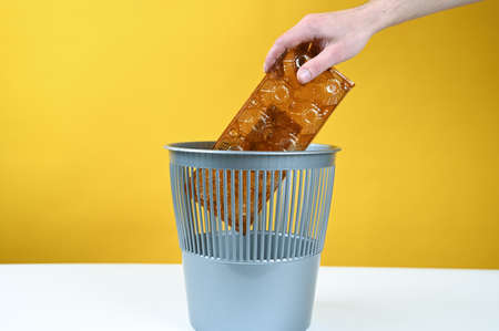 Hand throws out a plastic container for eggs in the trash bin. High quality photo 版權商用圖片