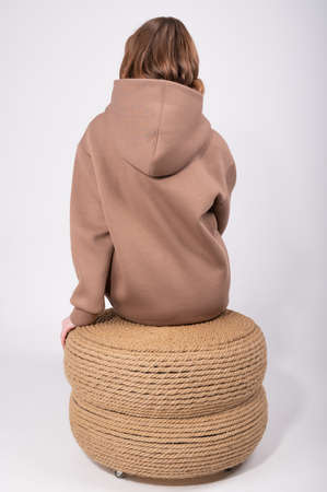 Back view of young woman in taupe hoodie sitting on pouf in white studio. High quality photo 版權商用圖片 - 167294887