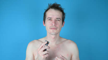 Portrait of young man on blue background. Shaving with wrong razor. High quality photo 版權商用圖片