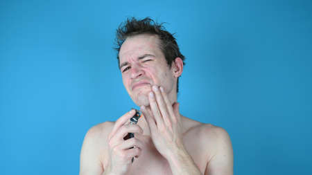 Young man in discomfort while shaving on blue background. High quality photo