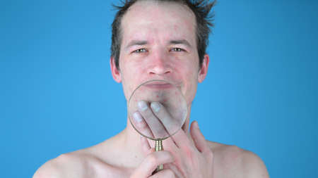 Young man shows irritation on his face through a magnifying glass. High quality photo 版權商用圖片