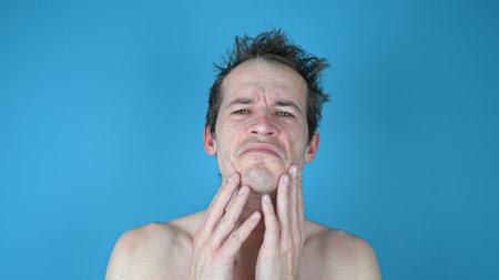 Portrait of a sad disgruntled man on blue background. Skin irritation after shaving on mans skin. High quality photo