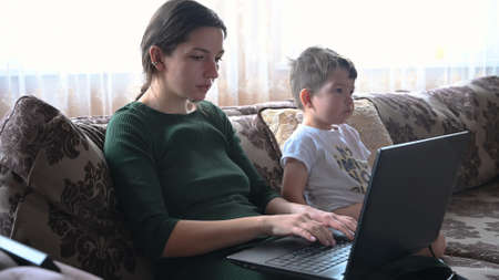 Young mother working from home with baby. High quality photo