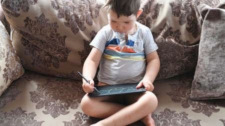 Little child learns to draw on a tablet. High quality 4k footage