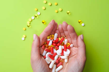 Cropped view of woman hands holding a lots of pills or vitamins on pastel green background. High quality photo