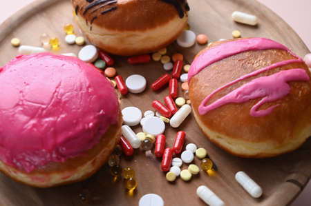 Glazed donuts and pills lie together on a wooden plate. Medicaments and sweets. Concept of addiction. High quality photo 版權商用圖片