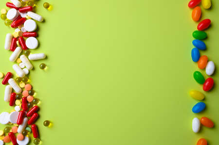 Top view of colorful bright pills and vitamins on pastel green background. High quality photo