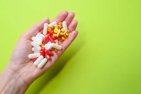 Close up of female hand holding many multi-colored pills on a green background. Health care concept. High quality photo
