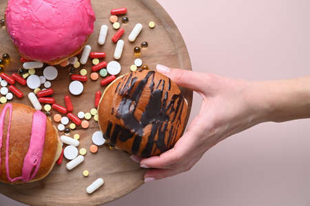 Womans hand takes tasty donut on pink background. Health care concept. High quality photo