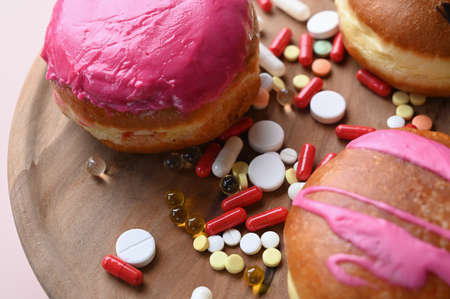 Unhealthy and sweets. Glazed donuts and pills on wooden plate. High quality photo 版權商用圖片