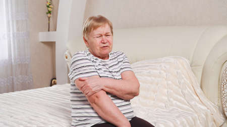 Elderly woman with pain in her arms.