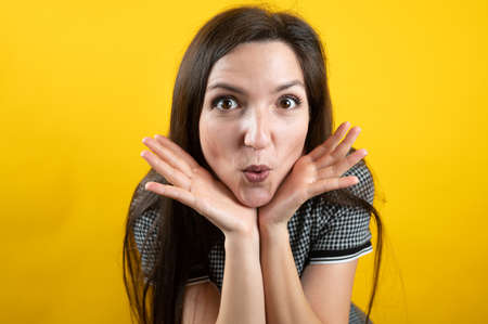 Young girl fooling around, on a yellow background.