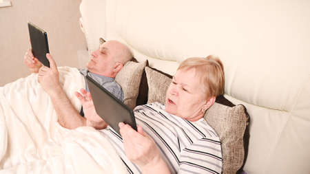 Modern elderly couple in bed