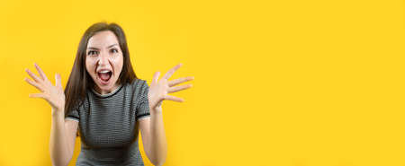 Portrait of a screaming young girl, on a yellow background