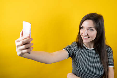A young girl communicates through a cell phone camera, on a yellow background