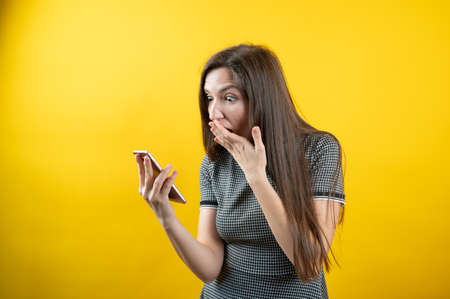 A young girl looks with surprise at a mobile phone, on a yellow background 版權商用圖片