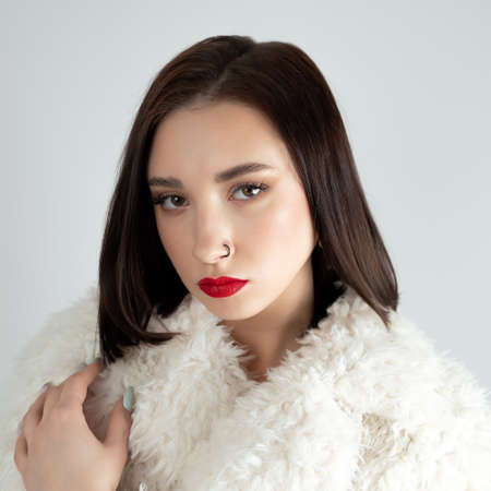Young woman with great shapes brows, long eyelashes and red lips. Brunette posing on white wall
